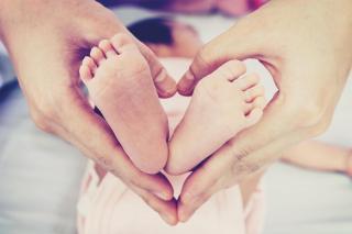 Hender holder babyføtter